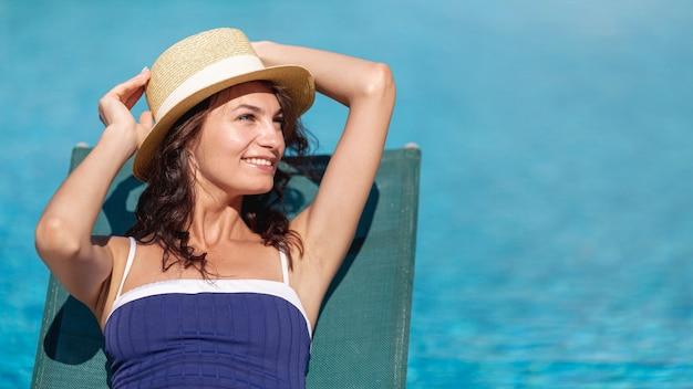 サンベッドに敷設の帽子を修正する女性