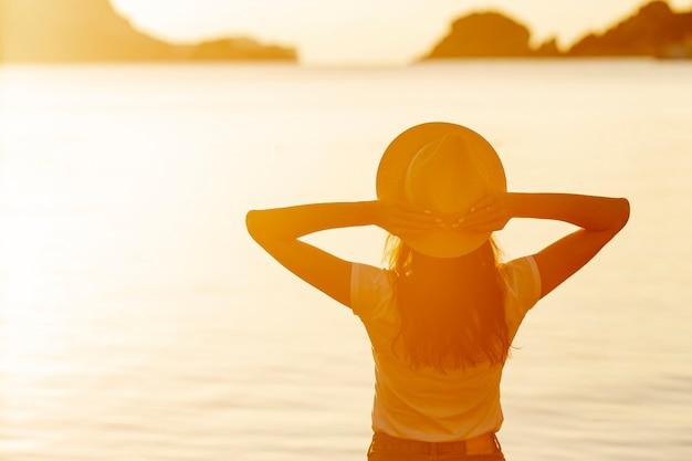 湖の岸に日没で帽子の女