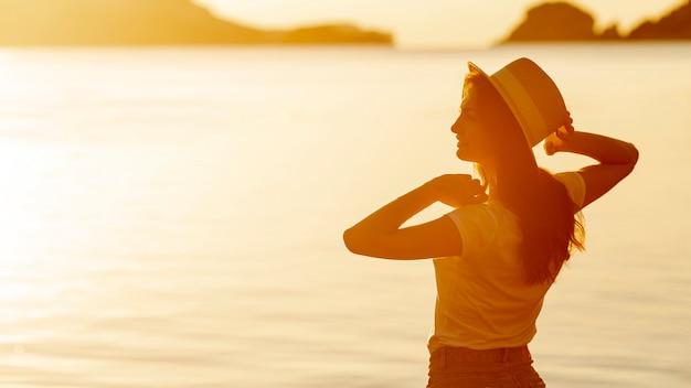 湖の岸に日没で帽子を持つ若い女性