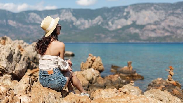 岩の上に帽子立っている身に着けている女性