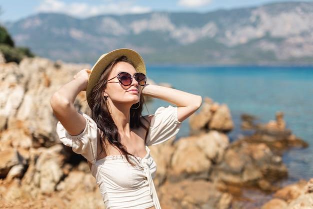 帽子と岩の上に立っているサングラスを着ている女性