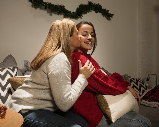 Мать целует дочь на рождество
