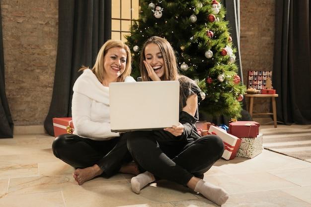 Счастливая мать и дочь, держа ноутбук