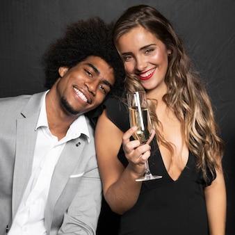 シャンパンのグラスを保持しているかわいいスマイリーカップル