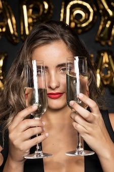 Крупным планом портрет девушки, держащей два стакана