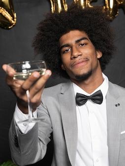 シャンパングラスを保持している美しいパーティースーツの男