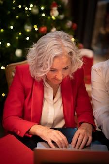 高齢者の女性が彼女のラップトップをチェック