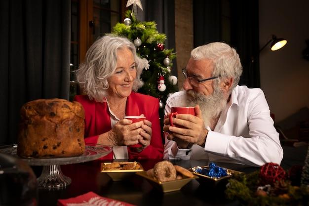 Старший мужчина и женщина празднуют рождество
