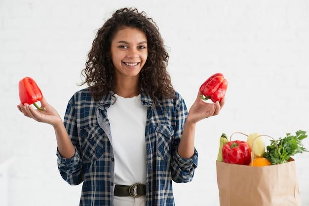 Вскользь одетая женщина держа красные перцы