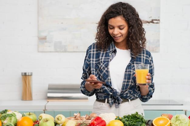 Красивый леди, проверка ее телефон рядом с овощами