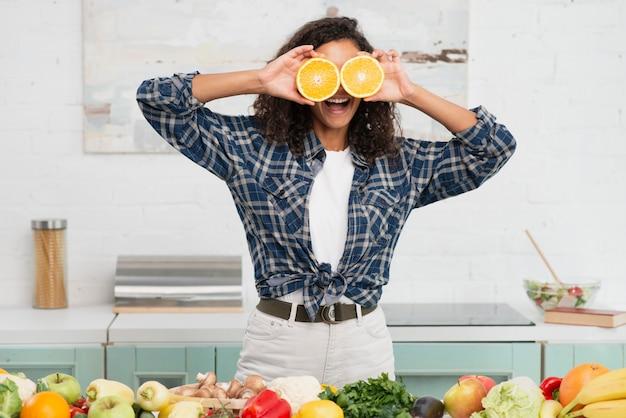 Женщина делает смешные лица с апельсинами