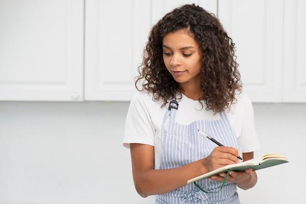 Афро-американская женщина пишет в тетради