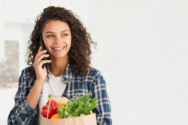 Женщина разговаривает по телефону и держит бумажный пакет