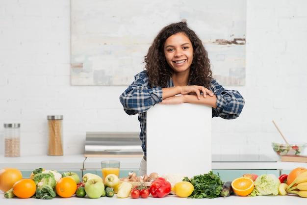 野菜の横にあるモックアップのサインを保持している女性