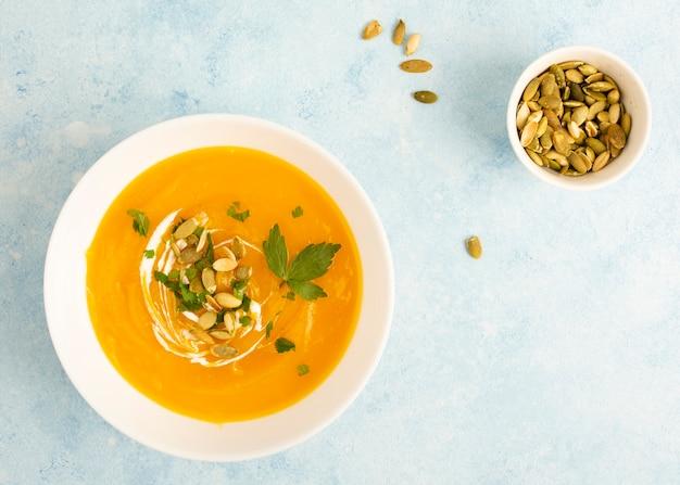 種子の横にあるクリームスープのトップビューボウル