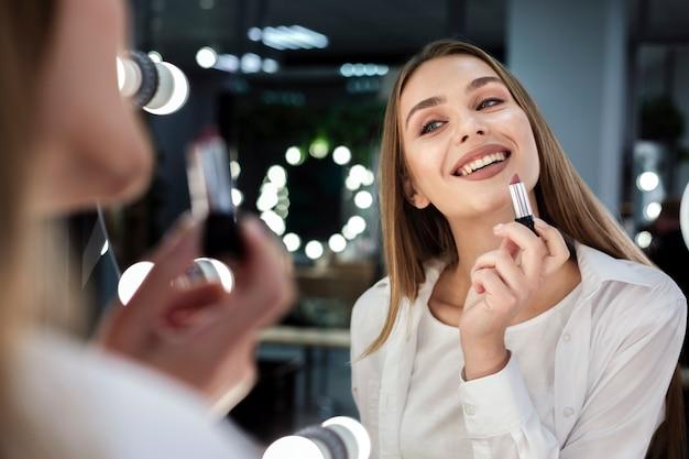 Женщина держит помаду, улыбаясь в зеркало