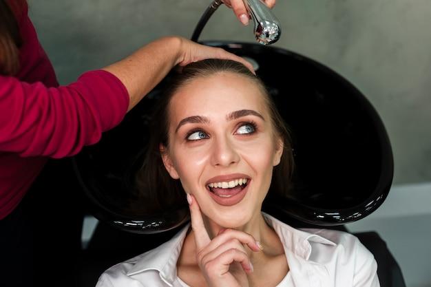 髪を洗って思慮深いブロンドの女性