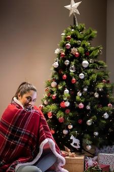 クリスマスツリーの横に座っている毛布を持つ若い女性