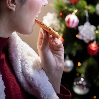 自宅でクッキーを食べるクローズアップ女性