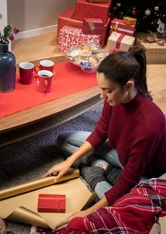 Женщина упаковывает подарок на праздник