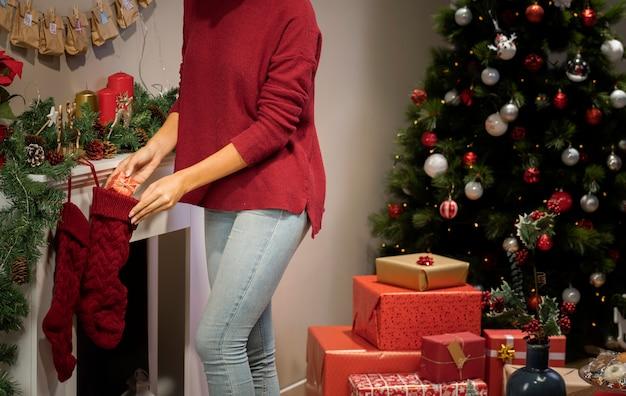 Женщина кладет подарок в рождественский чулок