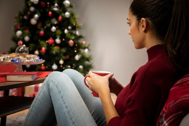 クリスマスの背景を持つカップを見て女性