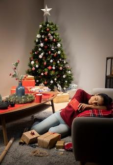 クリスマスの背景の赤いジャンパーに座っている女の子