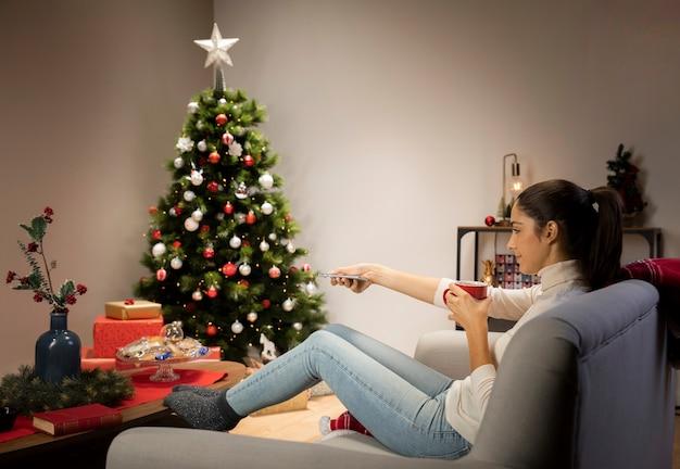 カップとクリスマスの背景を持つ女性