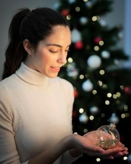 クリスマスグローブの装飾を保持している高角度の女性