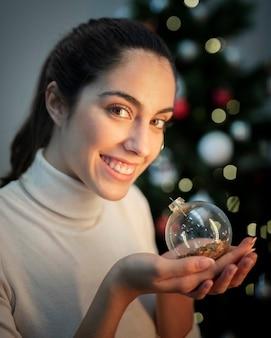 クリスマスグローブを保持しているスマイリーの若い女性