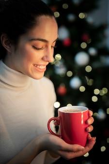 お茶とカップを保持しているスマイリーの若い女性