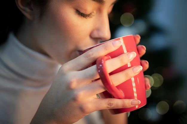 Вид сбоку молодая самка пьет чай
