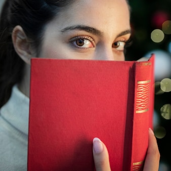 本で顔を覆っているクローズアップの若い女性