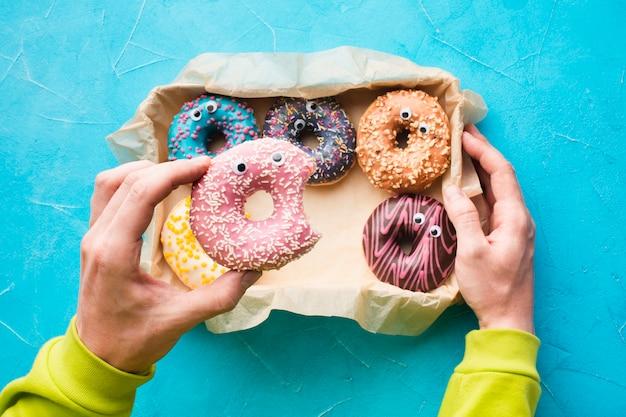Рука держит глазированный пончик