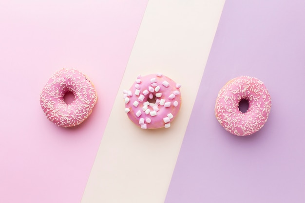 Вкусные розовые глазированные пончики вид сверху