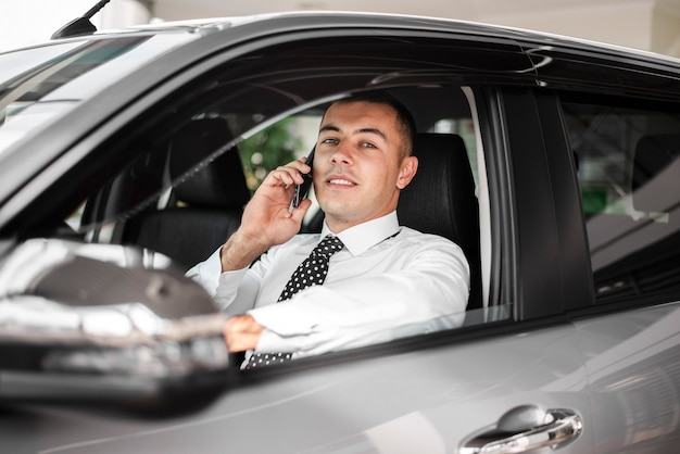 電話で話している車の中の正面若い男