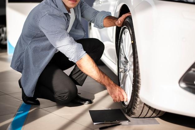 車のタイヤをチェックするクローズアップの若い男