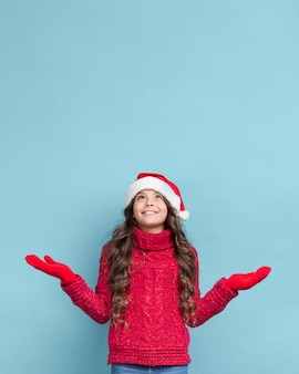 セーターとクリスマスの帽子を着ている少女