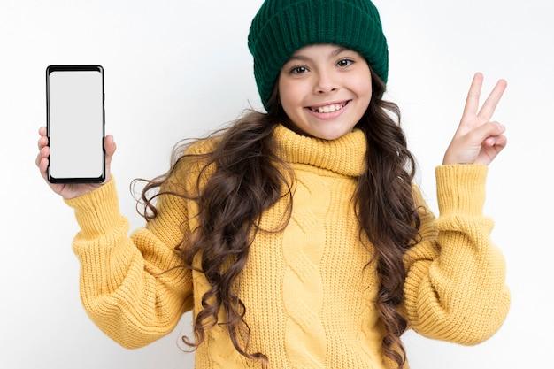 Улыбающаяся девушка держит телефон и показывает знак мира