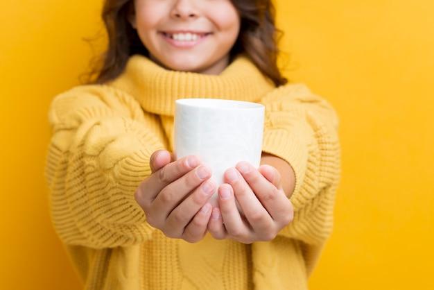 Крупным планом девушка держит чашку с горячим чаем