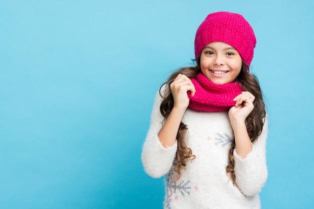 Улыбающаяся маленькая девочка в шляпе и шарфе