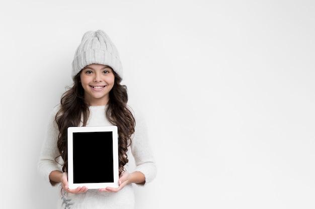 タブレットデバイスのモックアップを保持している少女