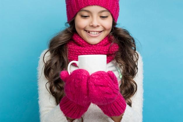 冬の服を着た少女の手でカップ