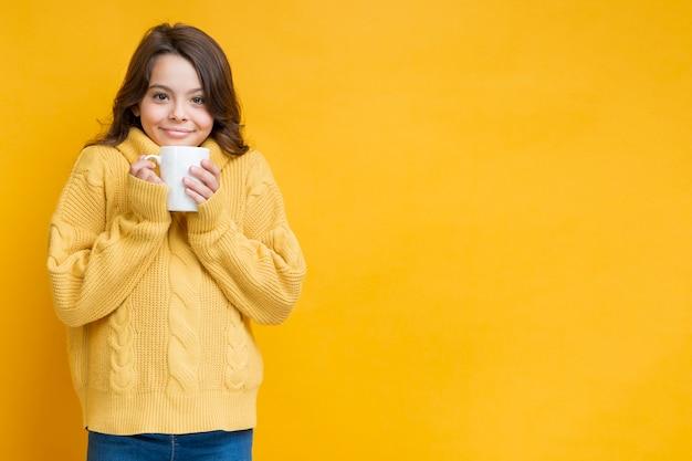 手でカップと黄色いセーターの女の子