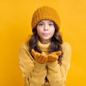 手袋とキスを吹いて冬の帽子を持つ少女