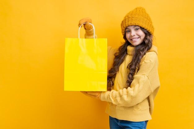 黄色の買い物袋でかわいい女の子