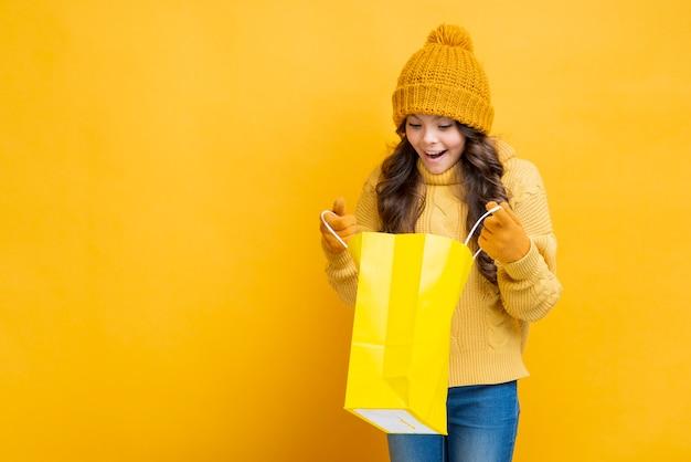 Девушка смотря в желтой хозяйственной сумке