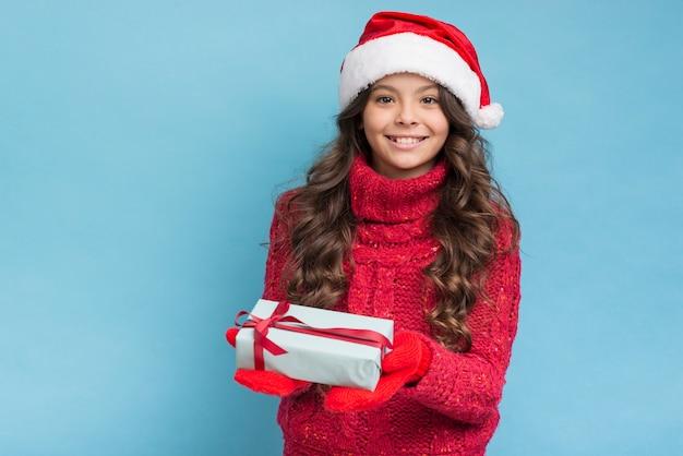 彼女の手に贈り物で幸せな女の子