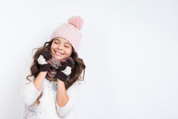 暖かい服を着て幸せなブルネットの少女