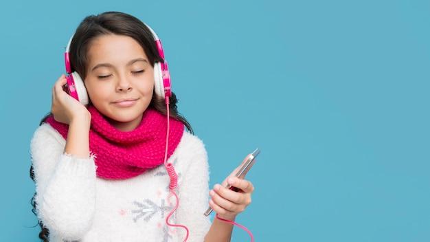 フロントビューの小さな女の子が音楽を聴く